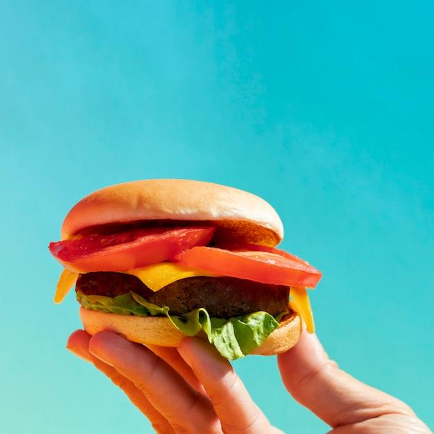 Persona del primo piano che ostacola cheeseburger