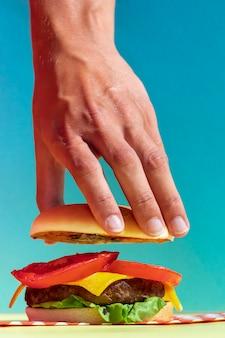 Persona del primo piano che ostacola il panino saporito dell'hamburger