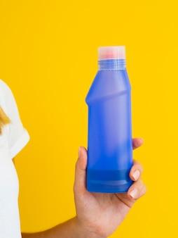 Persona del primo piano che ostacola la bottiglia detergente viola