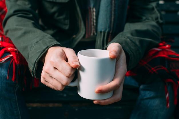 Persona del primo piano che ostacola tazza bianca