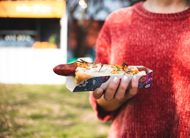 Persona del primo piano che ostacola un hot dog