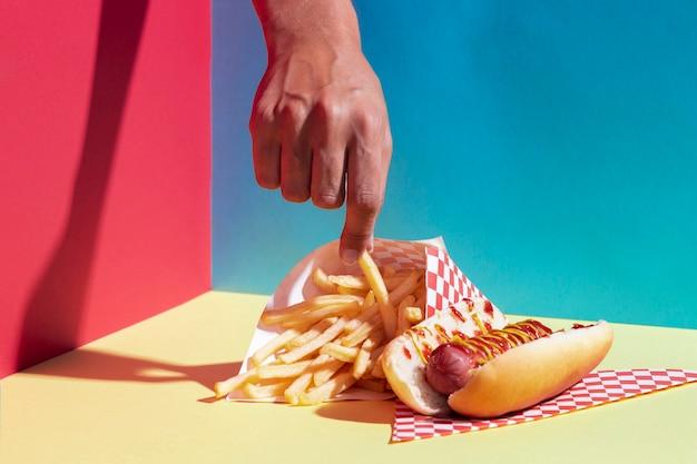 Persona del primo piano che ostacola una patata fritta