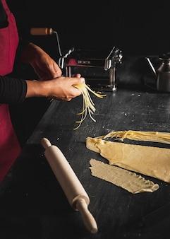 Persona del primo piano che prepara pasta