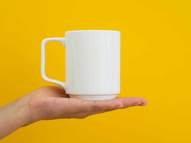 Persona del primo piano che sostiene tazza