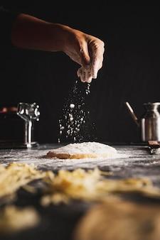 Persona del primo piano che spruzza farina su pasta