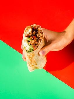 Persona del primo piano che tiene alimento messicano tradizionale