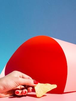 Persona del primo piano che tiene i chip di tortiglia