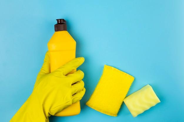 Persona del primo piano che tiene la bottiglia detergente gialla