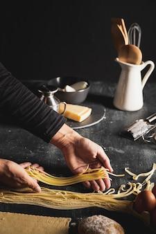 Persona del primo piano che tiene pasta per gli spaghetti