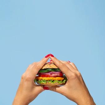 Persona del primo piano che tiene un hamburger squisito della verdura