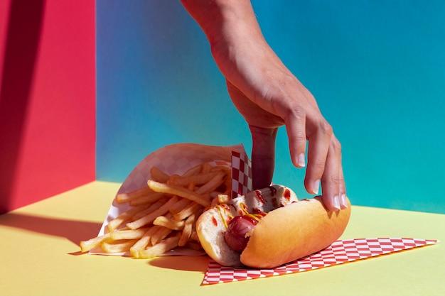 Persona del primo piano con hot dog e patatine fritte