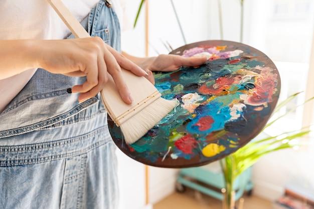 Persona del primo piano con la tavolozza e la spazzola della pittura