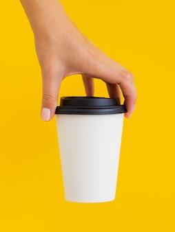 Persona del primo piano con la tazza e la priorità bassa gialla
