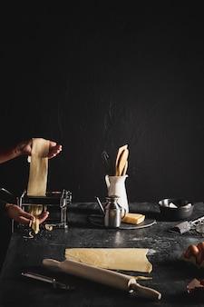 Persona del primo piano con pasta e utensili da cucina