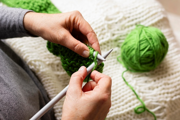 Persona di alta vista che lavora a maglia con filo verde
