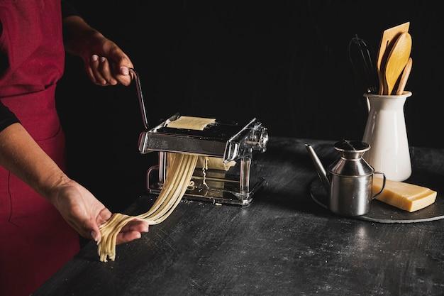 Persona di close-up con macchina per la pasta e utensili da cucina