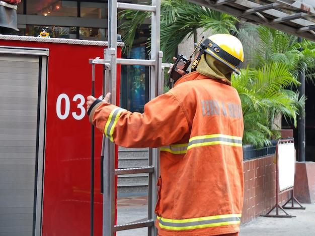 Persona di fuoco e soccorso con camion dei pompieri.