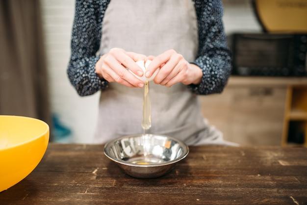 Persona di sesso femminile rompe l'uovo in una ciotola sul tavolo di legno. preparazione di cottura della torta dolce.