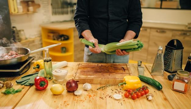 Persona di sesso maschile che cucina carne con verdure in padella