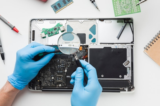 Persona di vista superiore che ripara un computer portatile