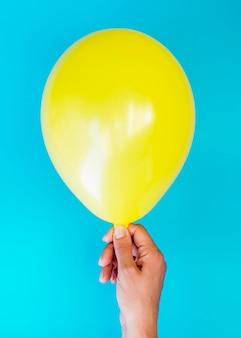 Persona di vista superiore che tiene pallone giallo