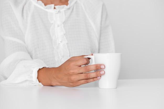 Persona in camicia bianca che tiene una tazza