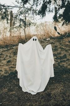 Persona in costume da fantasma in piedi nella foresta con le mani in alto