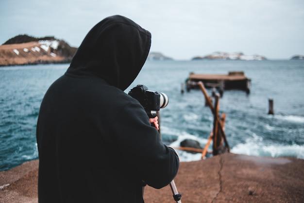 Persona in felpa con cappuccio nera che tiene la fotocamera dslr nera