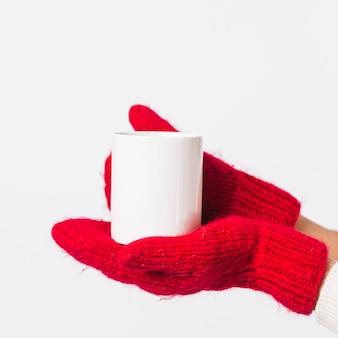 Persona in guanti che tiene tazza