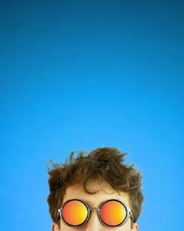 Persona in occhiali da sole con i capelli arruffati su sfondo blu sfumato