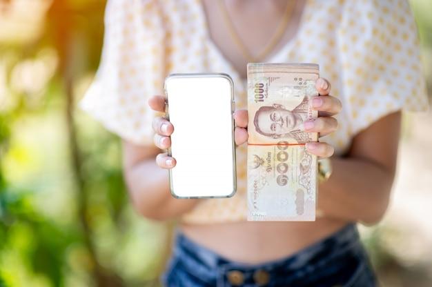 Persona in possesso di banconote e smartphone