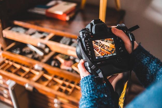 Persona in possesso di fotocamera digitale nera