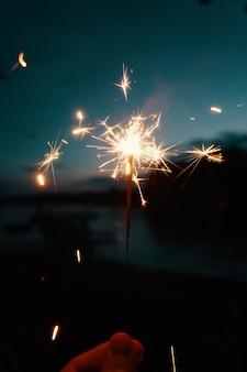 Persona in possesso di luci del bengala o stelle filanti su uno sfondo sfocato scuro