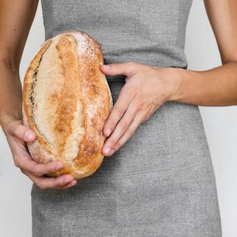 Persona in possesso di pagnotta di pane