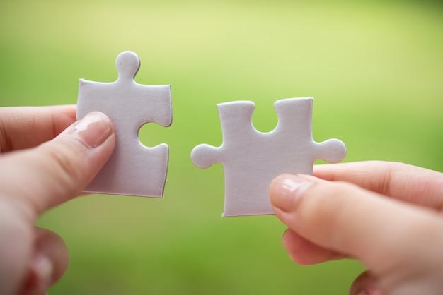Persona in possesso di pezzi del puzzle bianco
