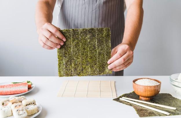 Persona in possesso di sushi nori