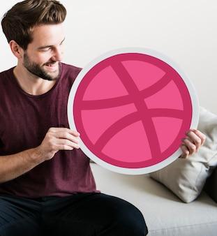 Persona in possesso di un icona di dribbble