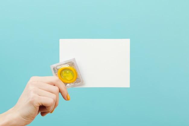 Persona in possesso di una carta vuota e un preservativo
