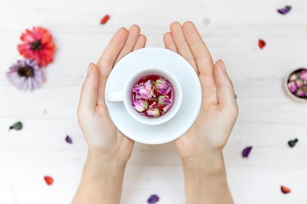 Persona in possesso di una tazza da tè bianco con petali di rosa