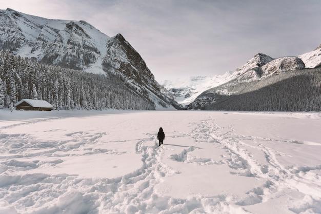 Persona in valle innevata in montagna