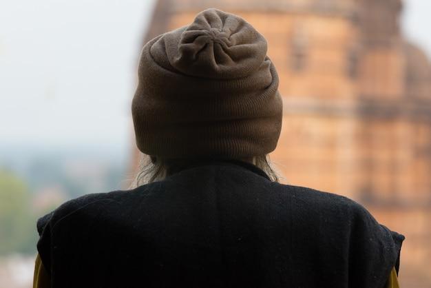 Persona indiana che esamina tempio, retrovisione, india.