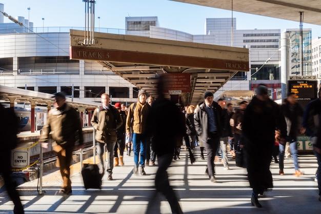 Persona irriconoscibile e turista in visita alla stazione sud a piedi fuori dal treno nella stazione, a boston, massachusetts, usa.