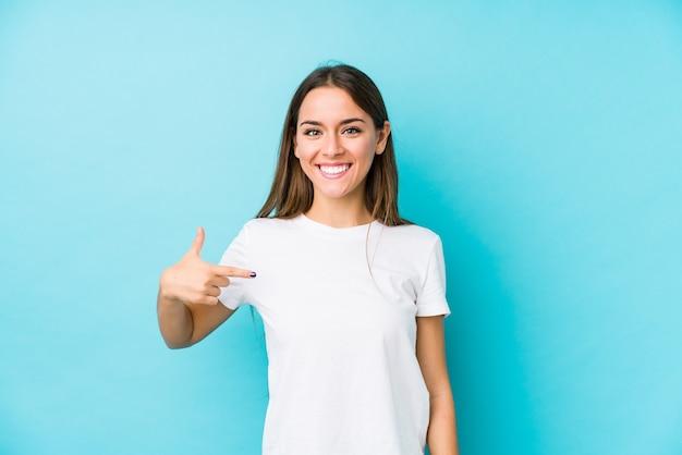 Persona isolata giovane donna caucasica che indica a mano uno spazio della copia della camicia, fiero e sicuro