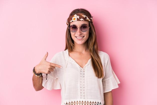 Persona isolata giovane donna caucasica dei pantaloni a vita bassa che indica a mano uno spazio della copia della camicia, fiero e sicuro