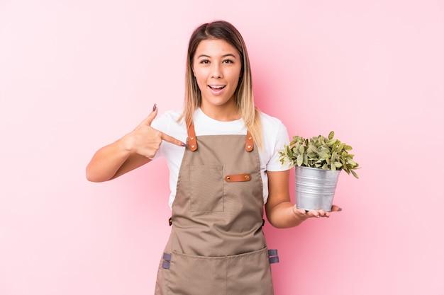 Persona isolata giovane donna caucasica del giardiniere che indica a mano uno spazio della copia della camicia, fiero e sicuro