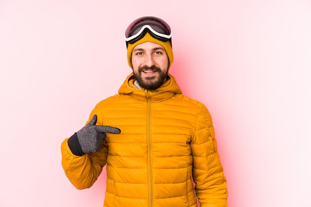 Persona isolata giovane sciatore che indica a mano uno spazio della copia della camicia, fiero e sicuro
