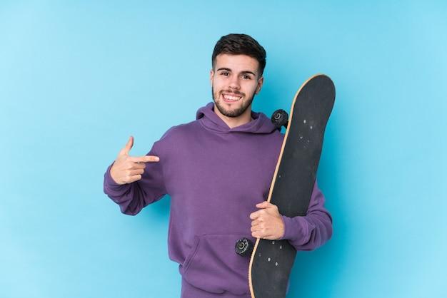 Persona isolata giovane uomo caucasico pattinatore che punta a mano uno spazio di copia camicia, orgoglioso e fiducioso
