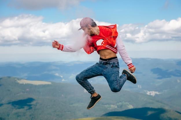Persona maschio felice insolita bizzarra strana che salta in cielo. uomo del viaggiatore che fuma sigaretta elettronica sopra la montagna.