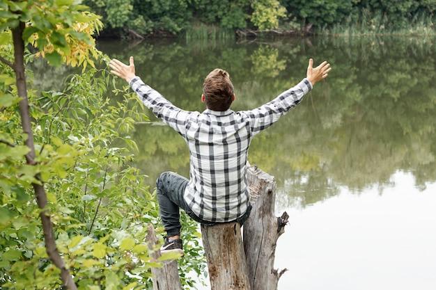 Persona seduta su un albero con le mani spalancate