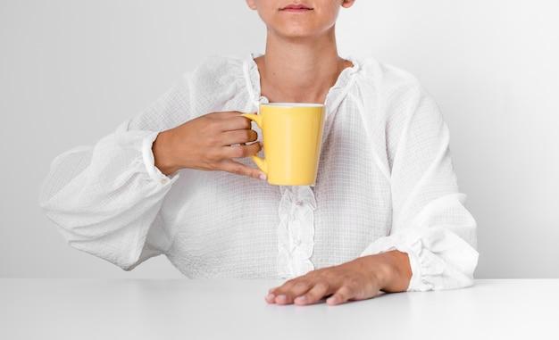 Persona seria di vista frontale che tiene una tazza